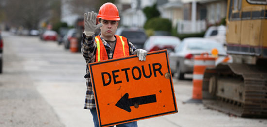 road worker holding detour sign in construction zone