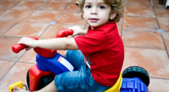 child riding toy tricycle